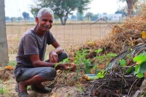 happy man kneeling in garden